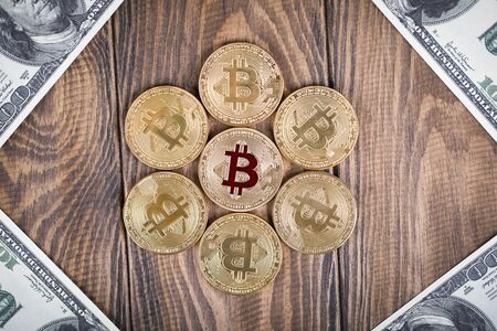 The cryptocurrency Bitcoin coin. Gold coin. 100 dollar bills lie in the corners.