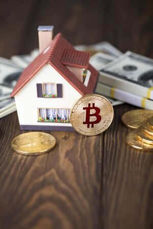The cryptocurrency Bitcoin coin. Gold coins and packs of hundred dollar bills. A miniature copy of the house. Foto de archivo - 132055755