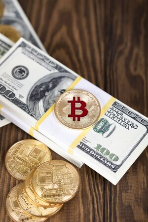 The cryptocurrency Bitcoin coin. Gold coin. Gold coin lies on a bundle of hundred-dollar bills.