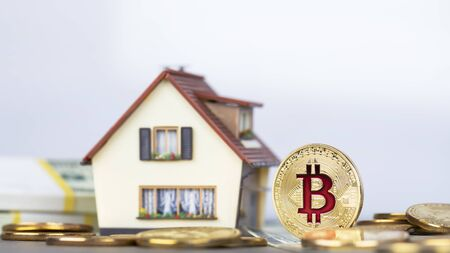 The cryptocurrency Bitcoin coin. Gold coins and packs of hundred dollar bills. A miniature copy of the house. Foto de archivo - 132056637