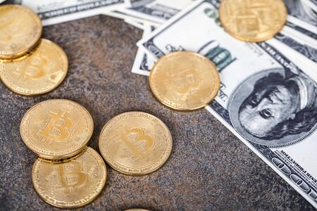 The cryptocurrency Bitcoin coin. Gold coins and packs of hundred dollar bills.