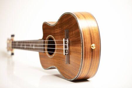Ukulele on a white background. Hawaiian guitar lies on the table. Stok Fotoğraf