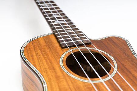 Ukulele on a white background. Hawaiian guitar lies on the table. Foto de archivo