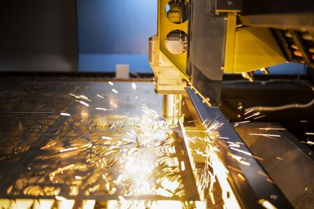 Automated programmed machine. Industrial laser machine cuts out parts in sheet steel. Heat. Sparks during operation of production machine at factory. 写真素材