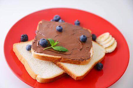 Toast with chocolate and nut paste and berry.