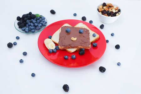 Toast with eyes and a smile. Toast with chocolate and nut paste. 스톡 콘텐츠