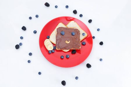 Toast with eyes and a smile. Toast with chocolate and nut paste. Imagens