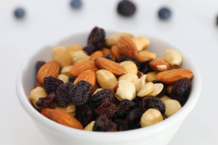Nuts and berries are scattered on the table. nuts are in the plate.