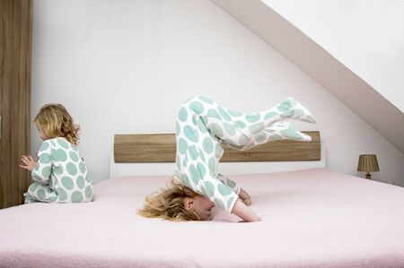 Two little sisters twins actively have fun on their parents beds, children in pajamas