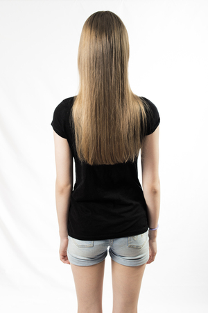 Girl stands with her back to the photographer, isolated on white