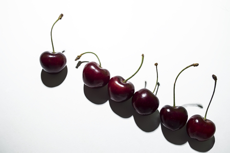 six bright, ripe cherries lie on the table diagonally