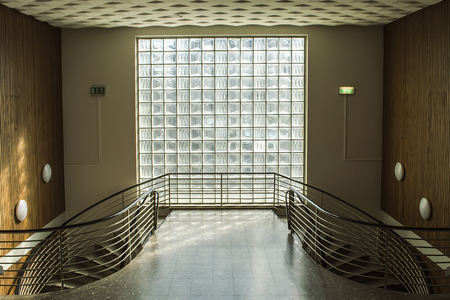Beautiful area with a double-sided staircase and a large window. Stock Photo