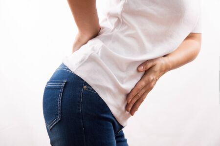 Man and his health, pain in the abdomen and back, the woman holds on to the stomach and lumbar
