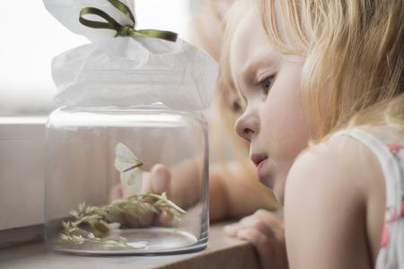 Girl looking at moth in a jar