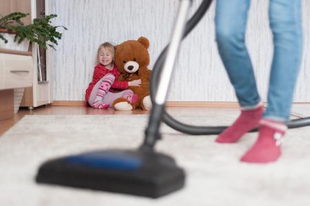 Donna che fa le pulizie di casa, aspira un tappeto con un pelo spesso