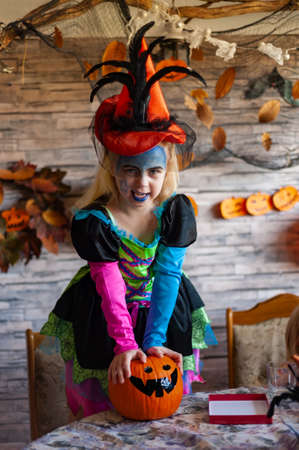 little witch, dressed up girl in a beautiful witch costume holds an orange pumpkin and makes a funny face Stock Photo
