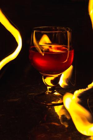 A glass of wine on a black background. Party club entertainment. Reklamní fotografie