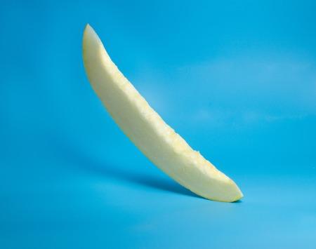 Slice fresh melon fly. On blue background Foto de archivo