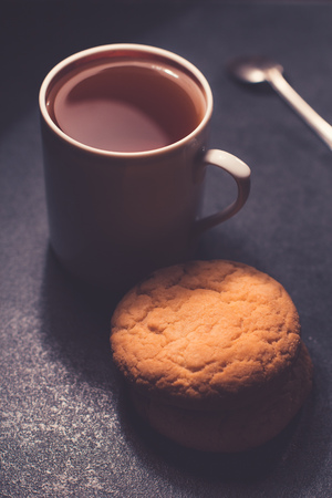 A glass cup of black tea with cookies. On a dark greyish marble background.