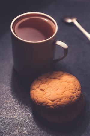Una taza de té negro con galletas. Sobre un fondo de mármol grisáceo oscuro. Foto de archivo - 109737154