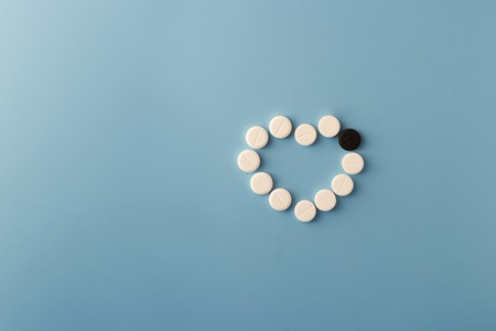 Abstract heart made of pills on a blue background