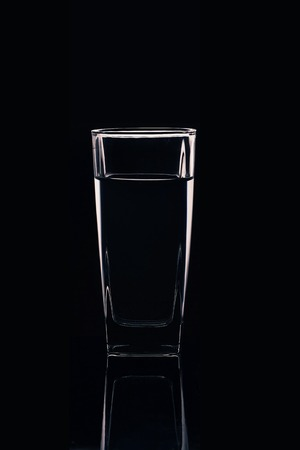 Silhouette of a glass with water on a black background Banque d'images