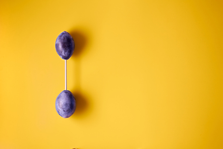 Barbell from plums on a yellow background Banque d'images