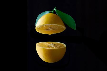 lemon fruit with leaf isolated on black background