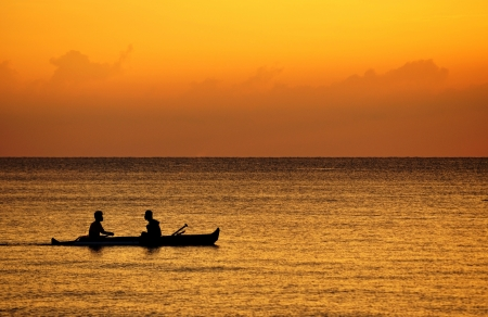 Silhouette of fisherman on a boat photo