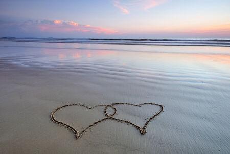 Love shape on a sand beach at sunset photo