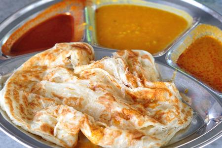 Roti canai flat bread, Indian food, made from wheat flour dough  Famous malaysian dish, Roti canai and curry
