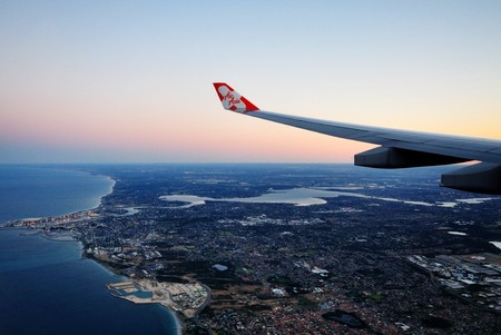 PERTH, AUSTRALIA  NOV 2 2010: AirAsia X wing with AirAsia logo, the plane flying over Perth skyline on November 2 2010. World Travel Award 2014 named AirAsia as Asias Leading Low Cost Airline.