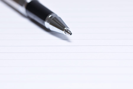 tip up: Close up of pen tip on a blank notebook Stock Photo