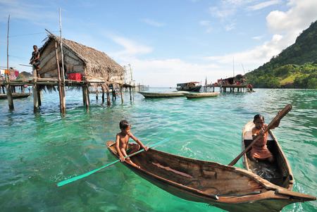 inhabit: SEMPORNA, SABAH, MALAYSIA - NOV 4 : Unidentified kids paddle a dug out boat on Nov 4, 2013 in Semporna, Sabah, Malaysia. They inhabit villages built on stilts in the middle of ocean.