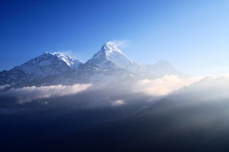 Dramatic sun light sunrise over snow capped mountain Machapuchare Fish Tail mountain in Annapurna Himalaya, taken during trekking to Poon Hill Nepal. photo