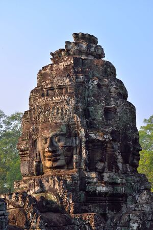 bass relief: Ancient Buddha faces in Bayon Temple, Angkor Wat Temple Complex, Siem Reap, Cambodia. Blue sky and forest tree as a background.