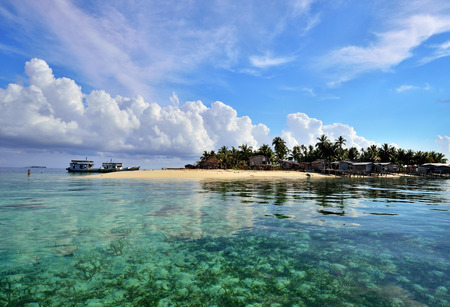 inhibited: Maiga Island scenery with dramatic clouds and clear turquoise water. Maiga island is a tropical island inhibited by Bajau Laut and Suluk located in Celebes sea Semporna Sabah Borneo Malaysia.