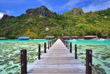 Long wooden pier heading toward Bohey Dulang Island in Sabah Borneo Malaysia.