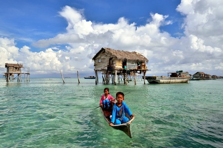 lived here: SABAH MALAYSIA  APR 19: Unidentified Bajau Laut kids on a boat in Bodgaya Island on April 19 2015. They lived in a house built on stilts in the middle of sea boat is the main transportation here. Editorial