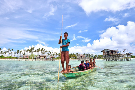 inhabit: SABAH MALAYSIA  APRIL 19: Unidentified Bajau Laut kids on a boat in Maiga Island on April 19 2015. They inhabit villages built on stilts in the middle of sea boat is the main transportation here. Editorial