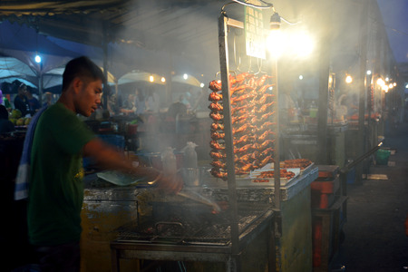 night market: KOTA KINABALU MALAYSIA  MARCH 27 2015: Local people  sell barbeque or grilled  chicken in Kota Kinabalu night market by the seafront in Sabah Borneo Malaysia
