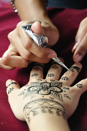 mehandi: Female henna artist applies a henna design to the back of a womans hands. Stock Photo