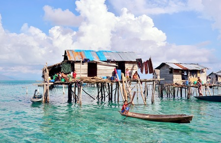 lived here: SABAH, MALAYSIA - APR 19: Unidentified Bajau Laut kid on a boat in Bodgaya Island on April 19, 2015. They lived in a house built on stilts in the middle of sea, boat is the main transportation here.