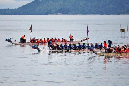 in unison: KOTA KINABALU, MALAYSIA - JUN 7, 2014 : Dragon Boat contestants racing to the finishing line during Sabah FCAS International Dragon Boat Race 2014 in Kota Kinabalu, Sabah, Malaysia.