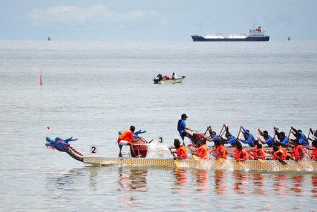 bateau de course: KOTA KINABALU, MALAYSIA - JUN 7, 2014 : Dragon Boat contestants racing to the finishing line during Sabah FCAS International Dragon Boat Race 2014 in Kota Kinabalu, Sabah, Malaysia.