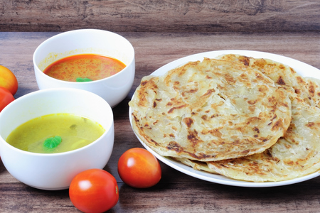 Roti canai or roti Prata with curry sauce and Dhal curry sauce, famous Malaysian food.