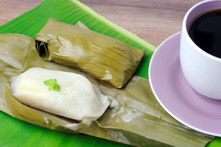 Kuih lepat pisang or also known as  Steam banana parcels cake with a cup of coffee, Kuih lepas pisang is a traditional Malaysian cake.