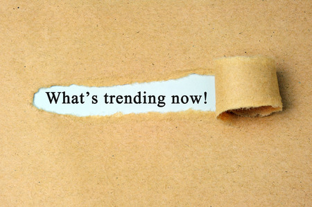 Ripped paper with whats trending now text. Stock Photo