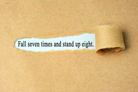 Ripped paper with  fall seven times and stand up eight text.