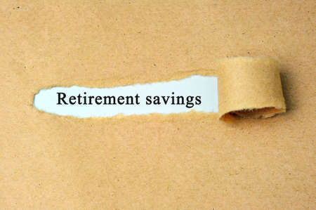 retirement savings: Torn paper with retirement savings text. Stock Photo